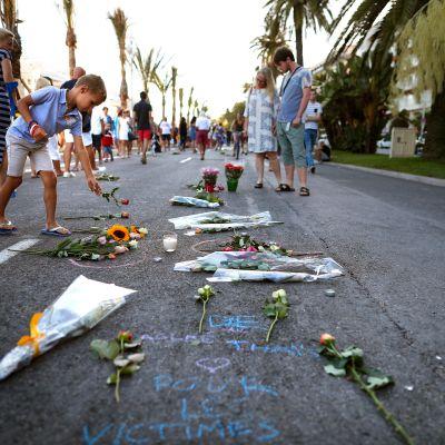 Poika laskee kukkia kadulle. Ympärillä kävelee ihmisiä.