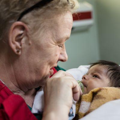 Sairaanhoitaja Kati Partanen pitelee pientä irakilaista vauvaa.