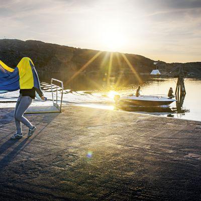 Två ungdomar som går med Sveriges flagga på huvudet intill en kaj.