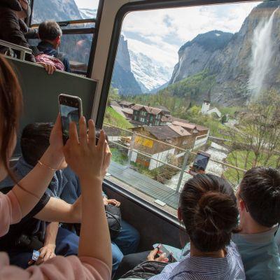 Turistit ottavat kuvia alppimaisemasta.