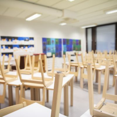 Luokkahuone jossa tuolit nostettu pöydille