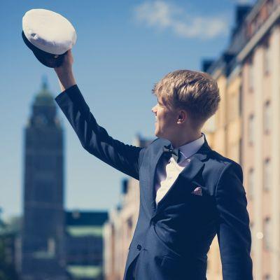 Student håller upp sin mössa mot Berghälls kyrka.