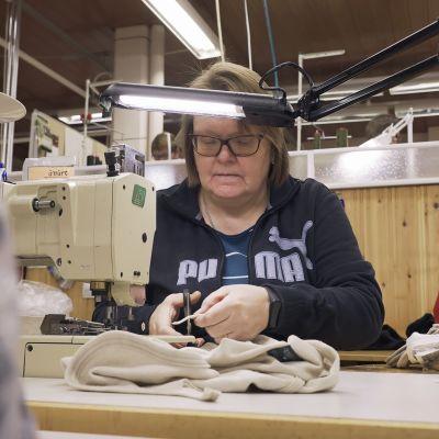 Nainen ompelee villaisia alusasuja Ruskovillan tehtaalla.