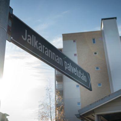 Lahden Jalkarannan palvelutalon kyltti joka osoittaa korkeaan rakennukseen.