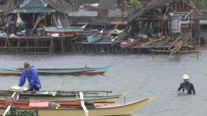 Översvämningar i Legazpi City i Filippinerna. En person hanterar en båt, en annan går omkring i vatten som når upp till midjan.