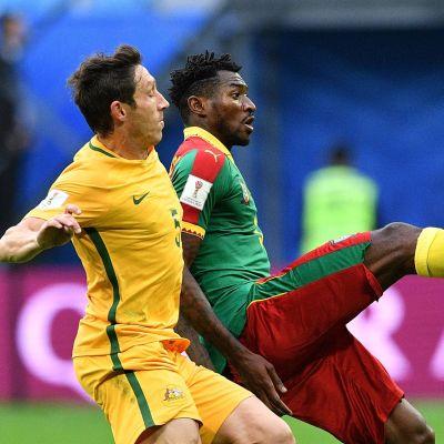 En grönklädd och en gulklädd fotbolsspelare i närkamp om bollen.