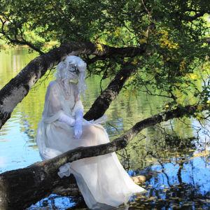 Hahmo istuu puunrungolla.