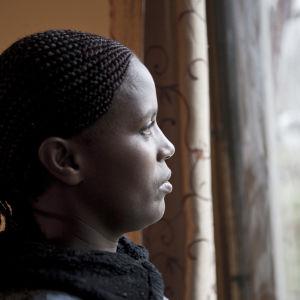 Nainen katsoo ulos ikkunasta.
