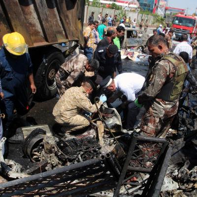 Räddningsarbetare i söker efter överlevande efter bombdåd i Basra i april 2016.