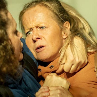 Två kvinnor brottas och griper varandra om nacken.