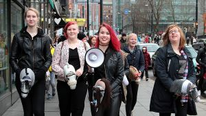 Alisa Aarniomäen järjestämän flash mobin osallistujia kävelee Helsingin keskustassa keppihevosineen. Alisalla megafoni kädessään.