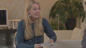 bloggari Nina Nordström olohuoneessaan kirja kädessä