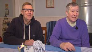 Två män sitter vid ett matbord.