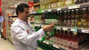 Butiksanställd plockar upp flaskor med äppelmust i hyllan.