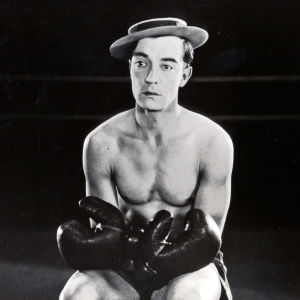 Buster Keaton istuu ilman paitaa, nyrkkeilyhanskat käsissään, lättähattu päässään. Kuva elokuvasta Rakkaus ja romahdus