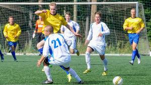 En fotbollsspelare stoppar en annan spelares framfart.