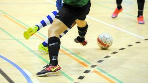 Futsalspelare fajtas om bollen.