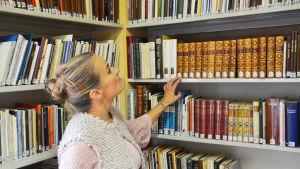 En blond kvinna står vid en bibliotekshylla fylld med böcker. Hon håller handen på en bokrygg och tittar uppåt mot böckerna ovanom henne.