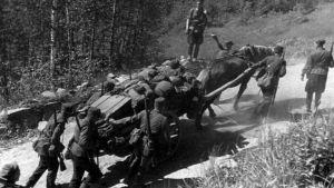 En häst dra en vagn med matrial och soldater hjälper till med att knuffa vagnen.