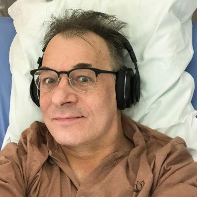 Kaj ligger i en sjukhussäng med hörlurar på sig. Han ser rakt in i kameran.