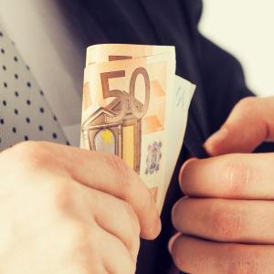 Man i kostym tar 50-eurossedel u kavajficka.