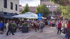 Mycket människor på en gågatan, de står eller sitter på stolar och bänker. Sommar. Byggnader runt omkring.