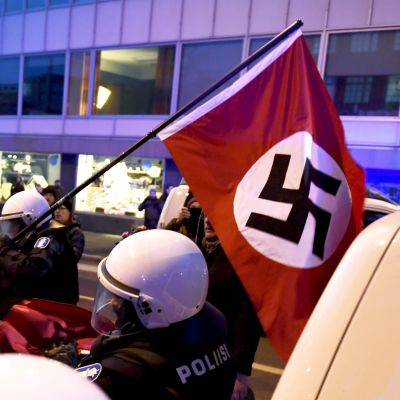 Nordiska motståndsrörelsen bär den nazistiska hakkorsflaggan under demonstration på självständighetsdagen 2018. Polisen griper in.