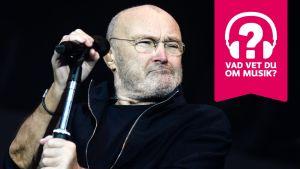 Phil Collins håller i en mikrofon som är i en mikrofonställning.