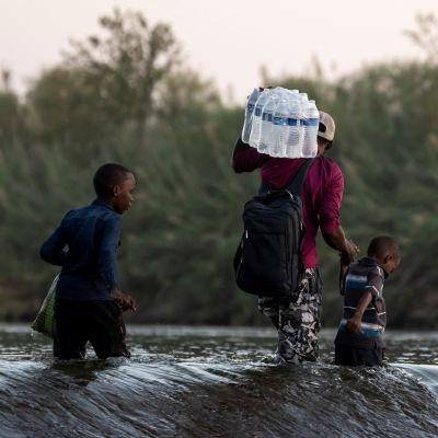 En man går i en flod och bär på vatten. Bredvid honom två barn.