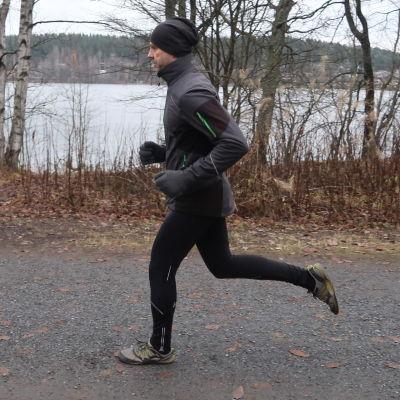 En person springer ute i höstmörkret. I bakgrunden syns träd utan löv och en sjö.