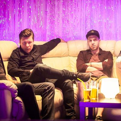 Modernit miehet istuvat baarin pitkällä sohvalla.