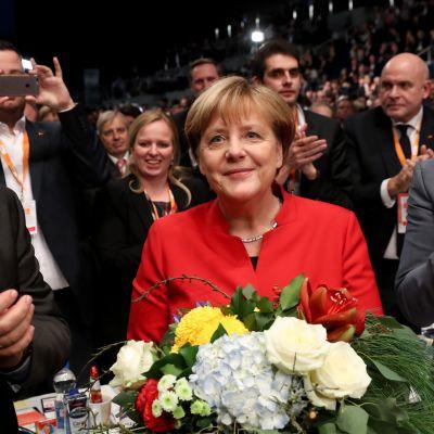 Merkel kukkakimppu sylissään. Ympärillä ihmisiä.