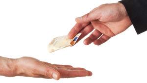 En femtioeurossedel överräcks från en hand till en annan.