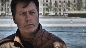 mörkhårig man i brun läderjacka vid vatten i Köpenhamn