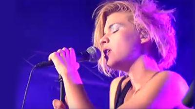 Blond kvinna med slutna ögon står på scen med en lila backlight, hon uppträder. Bilden är från axlarna uppåt.
