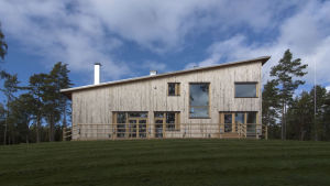 Villa Sundsvedja har en träfasad med stora fönster och snett tak.