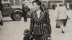 Jakkupukuun pukeutunut nainen kulkee lasta kädestä pitäen torin yli.