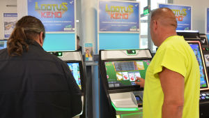 Två män spelar på spelmaskiner.