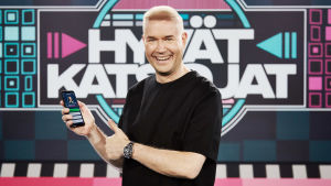 Marco Bjurström Hyvät katsojat -ohjelman lavasteessa, pitää kädessään kännykkää