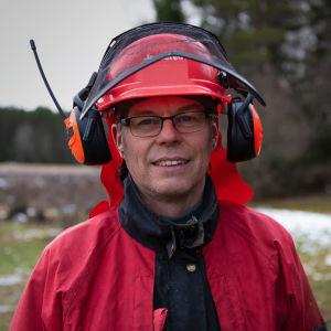 närbild av en man med glasögon, röd rock och en skogsarbetares skyddshjälm med tillhörande hörselskydd