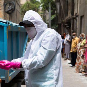 En kommunalt anställd i New Delhi får sina handskar desinficerade efter att han tagit hand om sopor i en lokal där man erbjuder coronatester. I bakgrunden står folk och köar för att testas.