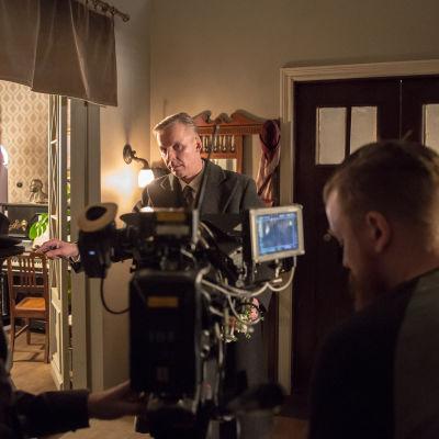 Neljä miestä ja elokuvakamera kodin lavasteissa.