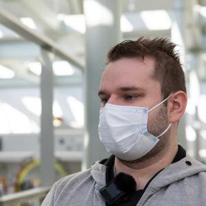 Studerande med grå huvtröja och munskydd.