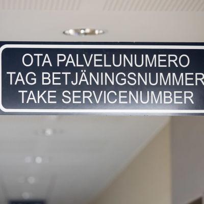 Ota palvelunuemro kyltti toimiston asiakaspalvelun katossa suomeksi, ruotsiksi ja englanniksi.