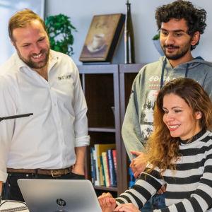 Kuvassa kolme ulkomaalaistaustaista työntekijää työpöydän ja tietokoneen ääressä keskustelemassa.
