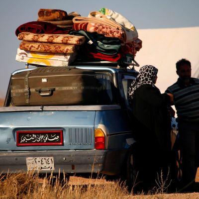 Syyrialaisia pakolaisia seisomassa täyteen pakatun autonsa vieressä lähellä Jordanian rajaa.