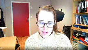 Stephanie Borenius, en dam med glasögon och en vit, norsk tröja, sitter på ett kontor med en bokhylla.