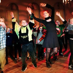 Laajassa kokokuvassa on lasten keskellä tanssimassa Aira Samulin. He kaikki ovat kohottaneet kätensä ylöspäin ja he heiluttavat käsiään.