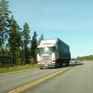 En lastbil och några personbilar kör på riksväg 25 i Horsbäck i Raseborg.