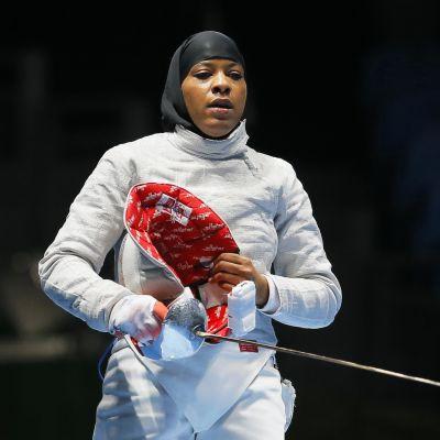 Ibtihaj seisoo miekkailuasussa säilä kädessään. Päässään hänellä on musta musliminaisten hijab-huivi.